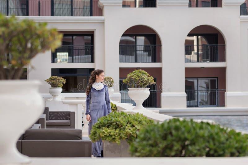 Eine junge Dame geht durch den Garten nahe einer alten Villa in einem altmodischen purpurroten Samtkleid der Weinlese stockfotos