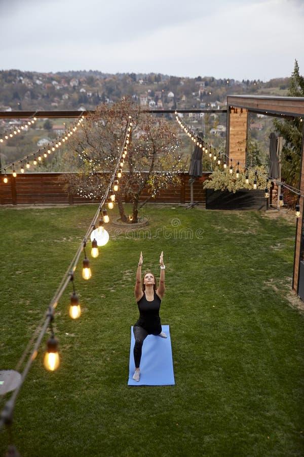 Eine junge Dame, 20-29 Jahre alt, Yoga Kriegers-Haltung, in einem Hinterhof eines fantastischen Hauses mit einer schönen Ansicht  lizenzfreies stockfoto