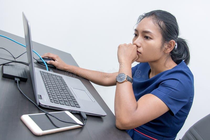 Eine junge durchdachte Frau betrachtet einen Laptop lizenzfreie stockbilder
