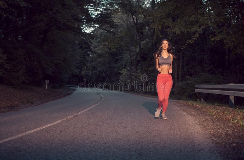 Eine junge erwachsene Frau, rüttelndes Laufen auf Asphaltstraße, draußen stockbild