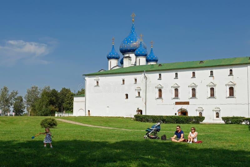 Eine junge Familie mit einem kleinen Kind, das auf dem Gras in Suzdal der Kreml sitzt Suzdal, Russland stockfoto