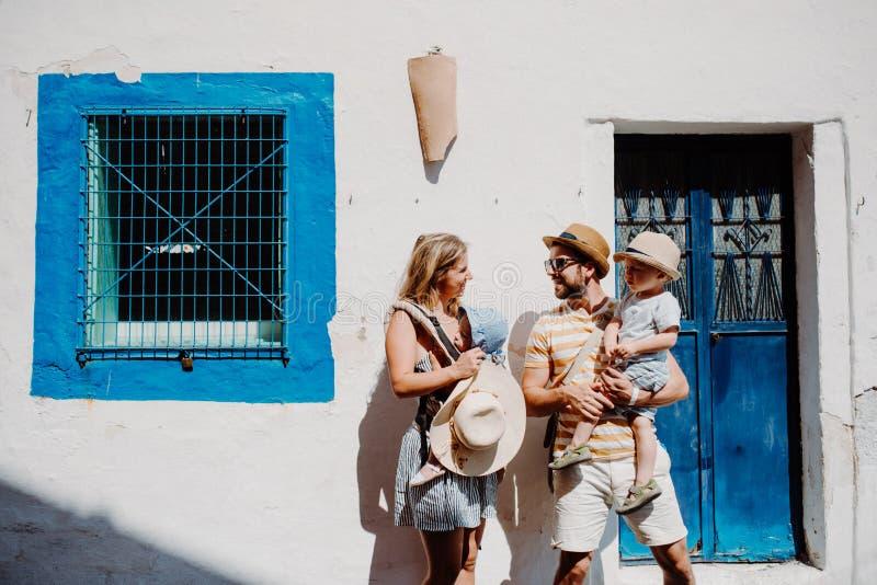Eine junge Familie mit zwei Kleinkindkindern, die in der Stadt an den Sommerferien stehen stockfoto