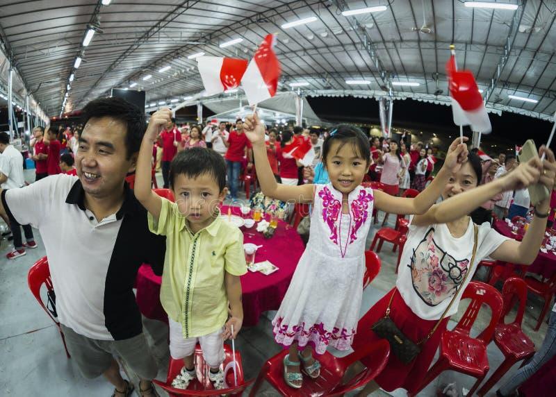 Eine junge Familie singen ein des Nationaltagliedes und bewegen Ministaatsflaggen mit Stolz und Freude wellenartig stockfotos