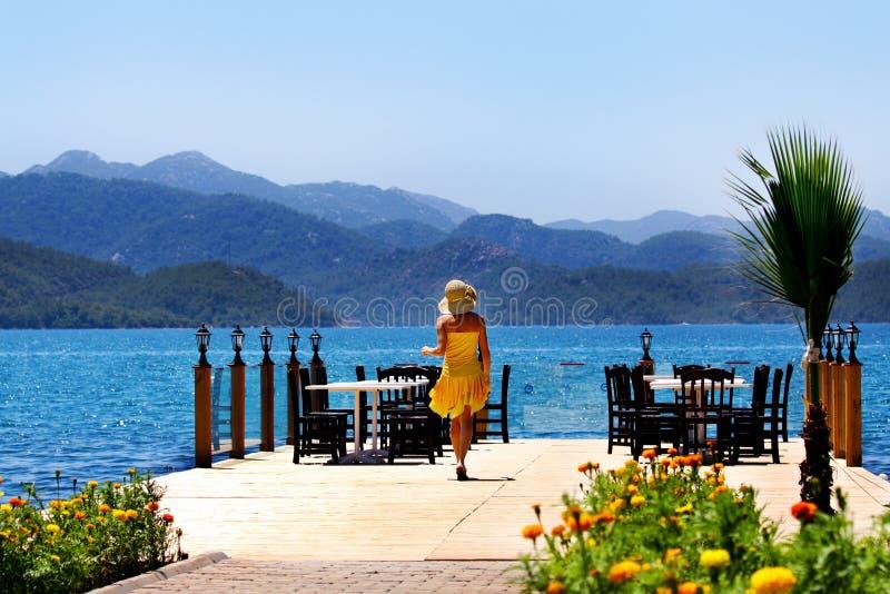 Eine junge Frau auf dem Pier lizenzfreie stockfotos