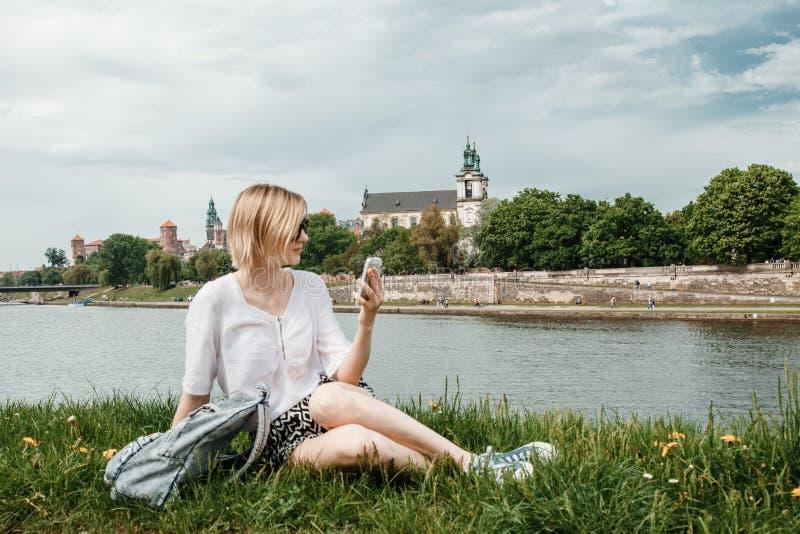Eine junge Frau auf der Weichsel in Krakau Stilvolles Mädchen in der Sonnenbrille spricht an ihrem Telefon Ansicht der Stadt von  lizenzfreie stockfotografie
