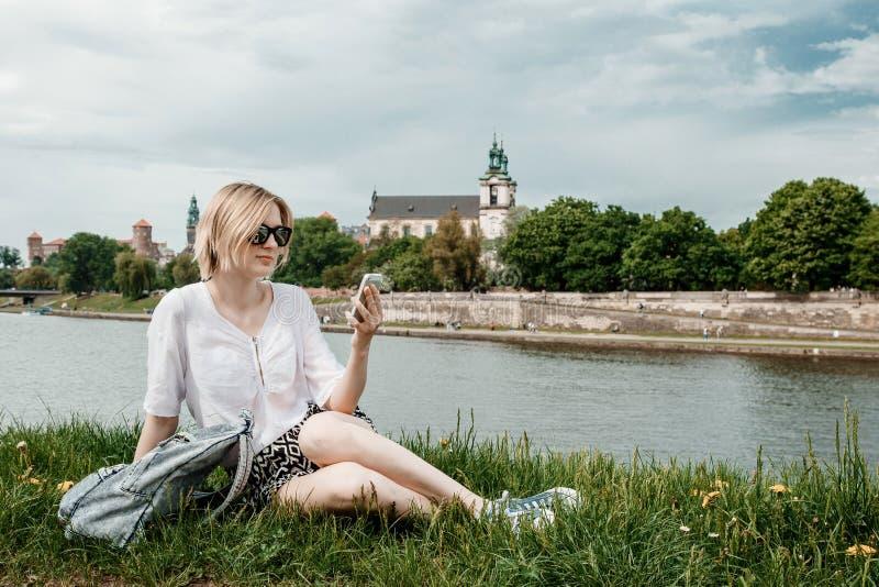 Eine junge Frau auf der Weichsel in Krakau Stilvolles Mädchen in der Sonnenbrille spricht an ihrem Telefon Ansicht der Stadt von  stockbilder