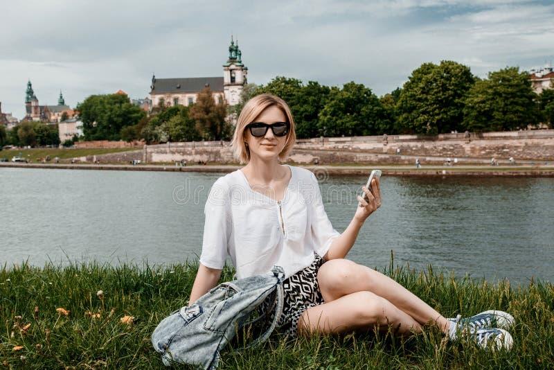 Eine junge Frau auf der Weichsel in Krakau Stilvolles Mädchen in der Sonnenbrille spricht an ihrem Telefon Ansicht der Stadt von  lizenzfreies stockbild