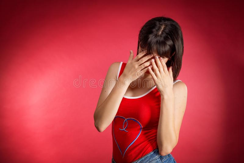 Eine junge Frau bedeckte ihr Gesicht mit ihren Händen, auf einem roten Hintergrund lizenzfreie stockfotografie