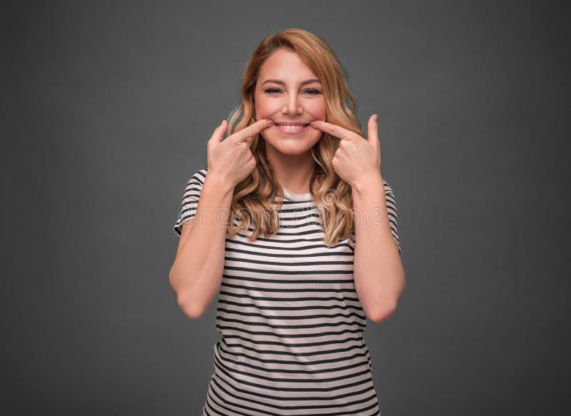 Eine junge Frau dehnt ihren Mund in einem falschen Lächeln gegen einen grauen Hintergrund aus Gefälschtes Lächeln stockfoto