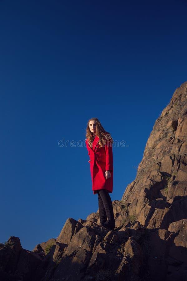 Eine junge Frau, die über einem Rand der steilen Klippe schaut lizenzfreie stockfotos
