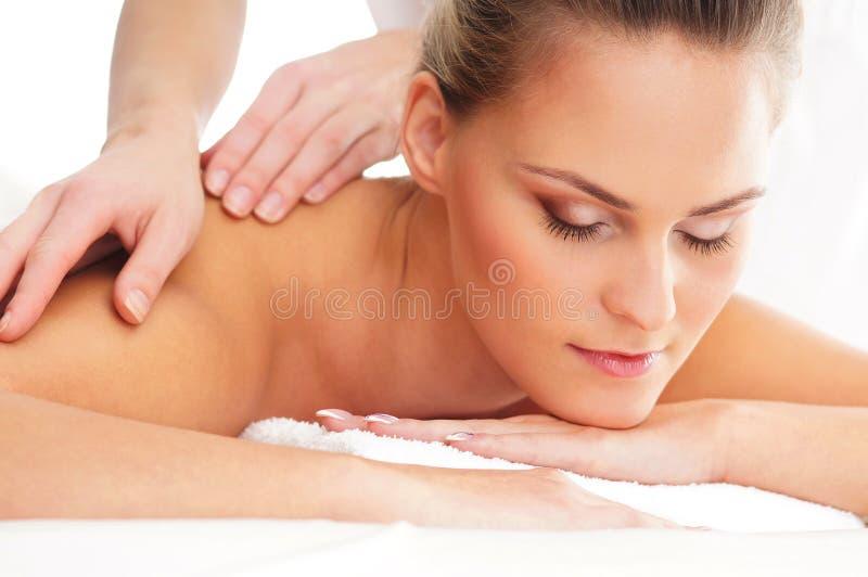 Eine junge Frau, die auf einer Badekurortmassage sich entspannt lizenzfreie stockfotografie