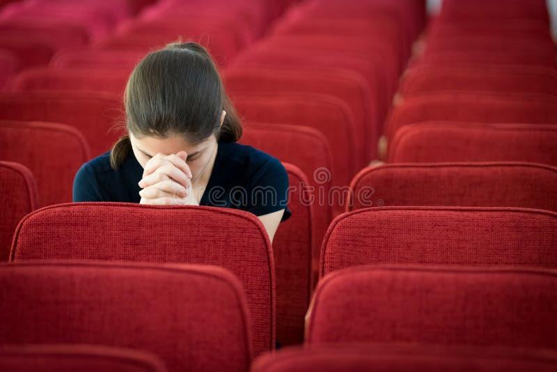 Eine junge Frau, die in einem betenden Stuhl sitzt lizenzfreie stockfotos