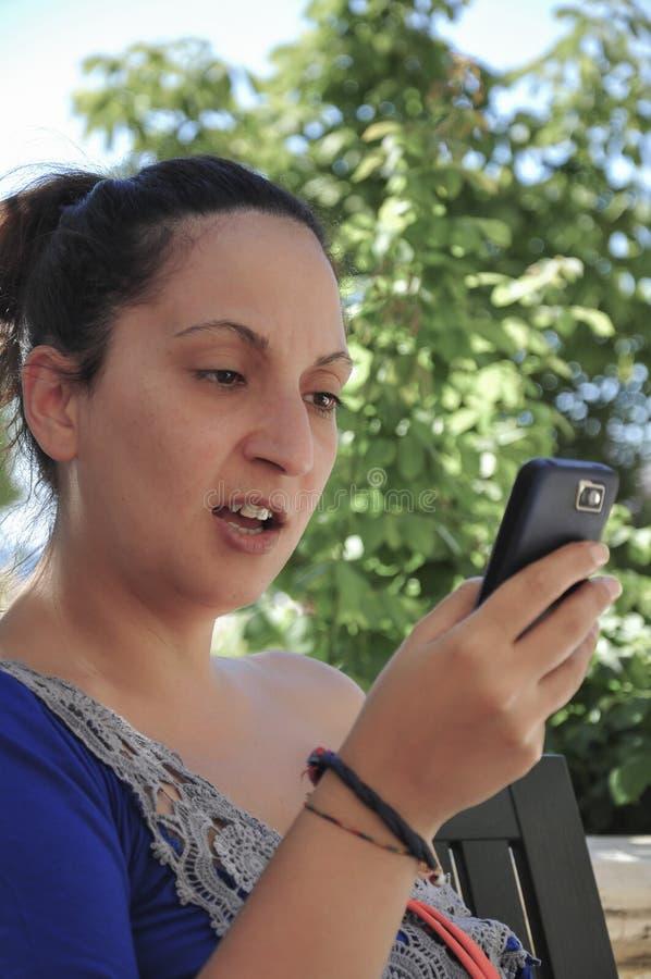 Eine junge Frau, die etwas an einem intelligenten Telefon schaut lizenzfreie stockbilder