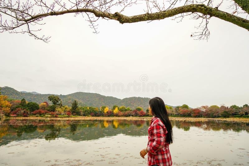 Eine junge Frau, die am Herbstpark genießt stockfotografie