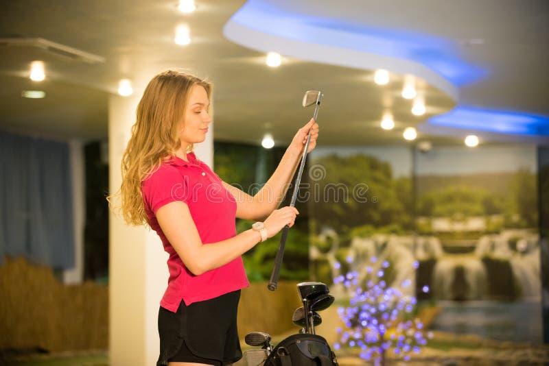 Eine junge Frau, die im Innenbereich Minigolf spielt. Ziehen Sie den Golfstick aus der Tasche und schauen Sie ihn an lizenzfreie stockfotos