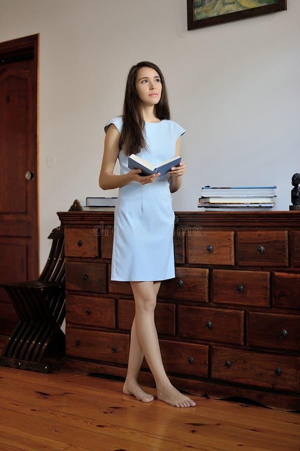 Eine junge Frau, die mit einem offenen Buch in ihren Händen steht stockbilder