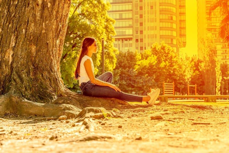 Eine junge Frau, die neben einem Baum sitzt und die Sonne genießt lizenzfreie stockfotografie