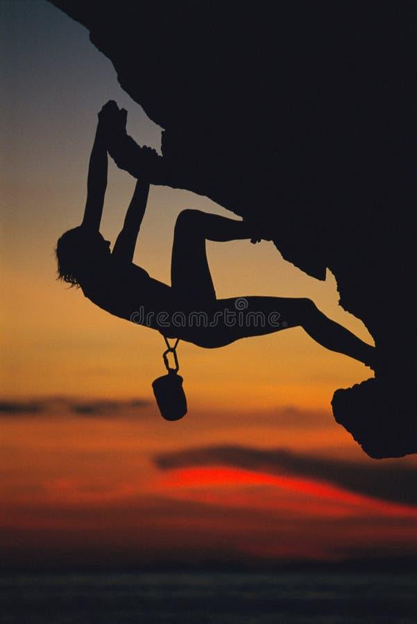 Eine junge Frau, die oben ein Felsengesicht steigt stockbilder