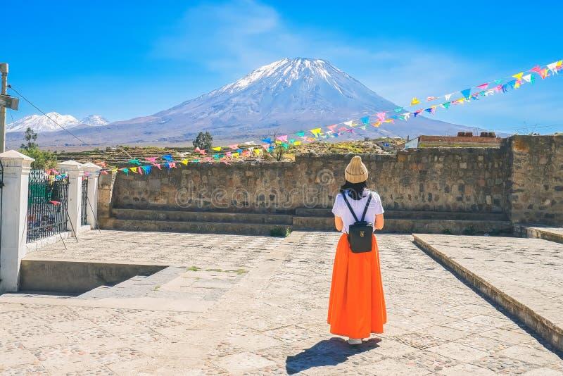 Eine junge Frau, die eine Pelzmütze und einen orange Rock trägt, bewundert das EL Misty Volcano in Arequipa, Peru stockbilder