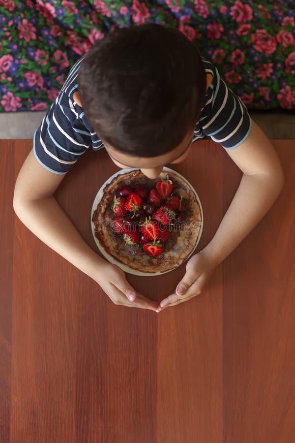 Eine junge Frau, die eine Platte von dünnen Pfannkuchen mit Erdbeeren und Schokoladencreme hält Weibliche Essenpfannkuchen mit fr stockfoto