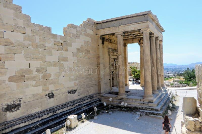 Eine junge Frau, die um die Akropolis durch den prachtvollen altgriechischen alten Tempel von Athene auf der Akropolise bewundern lizenzfreie stockfotografie