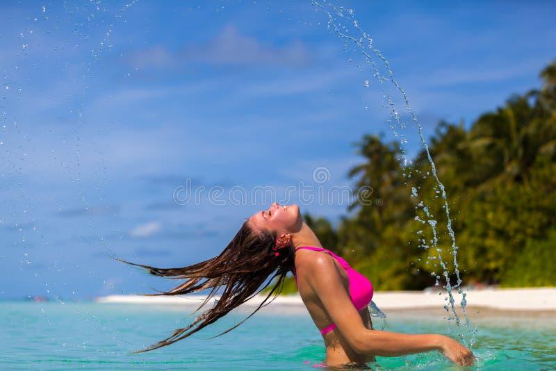 Eine junge Frau, die zurück ihr Haar wirft lizenzfreie stockfotos