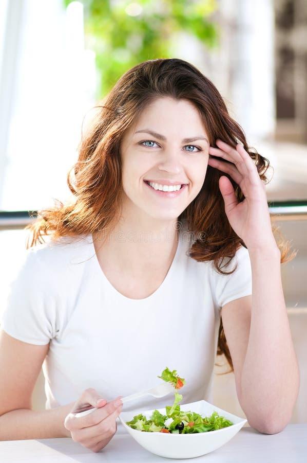 Eine junge Frau in einem Kaffee mit einem coffe mit Salat lizenzfreie stockbilder