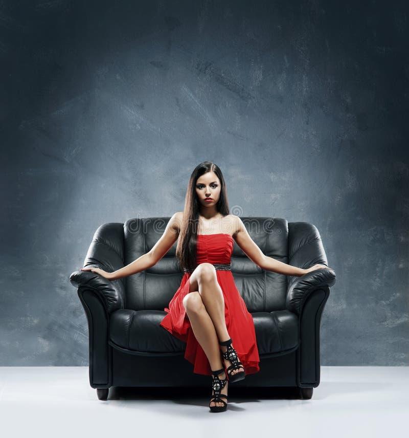 Eine junge Frau in einem roten Kleid, das auf einem Sofa sitzt lizenzfreies stockfoto