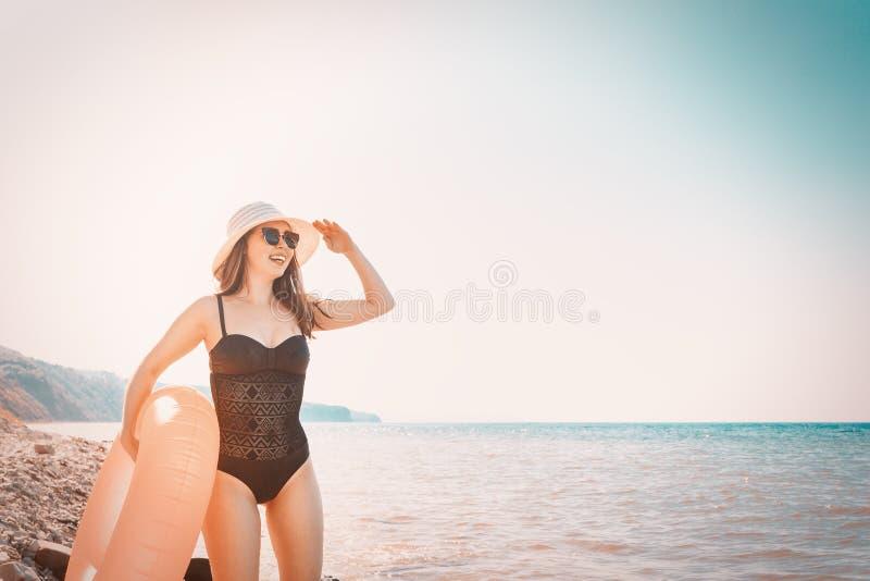 Eine junge Frau in einem schwarzen Badeanzug und in einem Hut, die einen orange schwimmenden Kreis halten und den Abstand untersu stockbilder