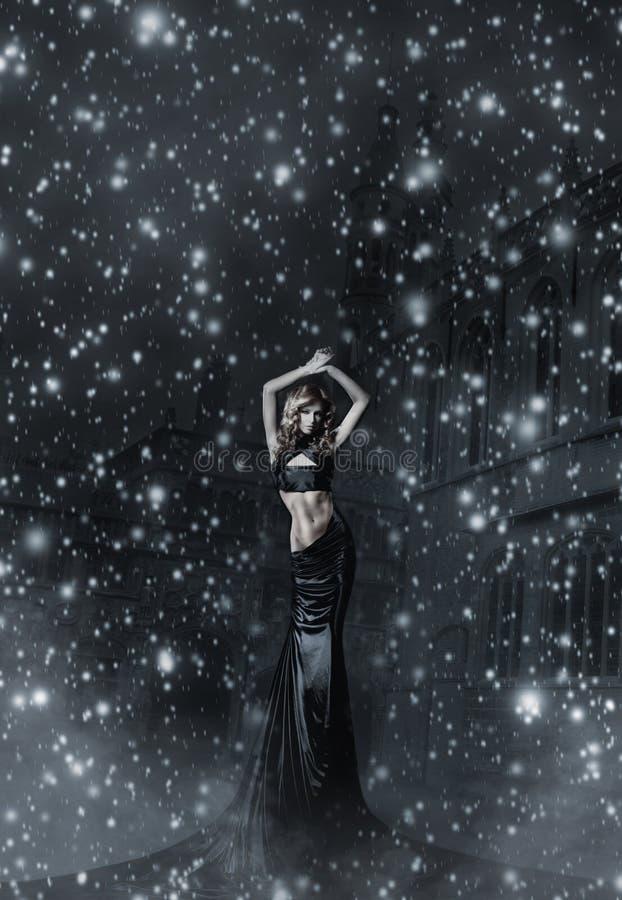 Eine junge Frau in einem schwarzen Kleid auf einem schneebedeckten Hintergrund stockbild