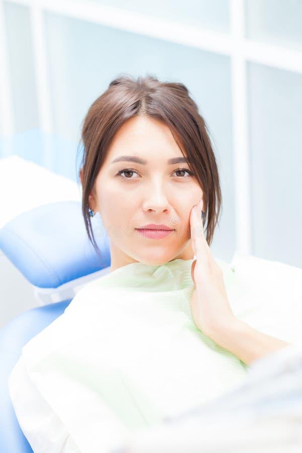 Eine junge Frau an einem Zahnarzt, der von der Zahnschmerzen sich beschwert stockfotos
