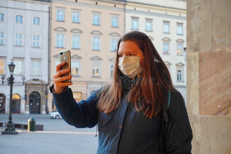 Eine junge Frau in einer medizinischen Maske fotografiert im Morgengrauen, sendet live oder kommuniziert über einen Videolink zum stockfoto