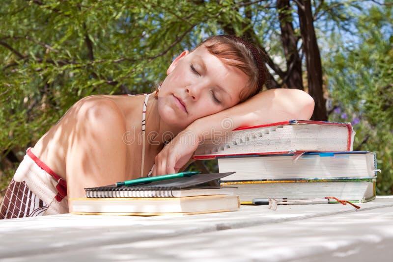 Eine junge Frau fällt schlafend, während studierend lizenzfreies stockfoto