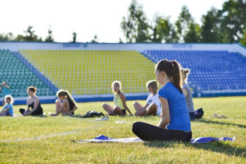 Eine junge Frau f?hrt Gymnastikyoga?bungen am Stadtstadion, Russland, Kursk-Region, Zheleznogorsk, im Juni 2018 durch lizenzfreie stockfotos