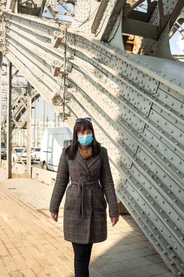Eine junge Frau geht in eine Schutzmaske ?ber der historischen Bolshokhotinsky-Br?cke in St Petersburg Es sch?tzt Gesundheit vor stockbilder