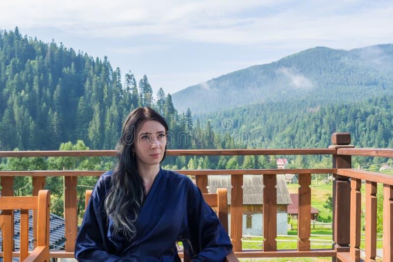 Eine junge Frau genießt eine Berglandschaft und sitzt in einem Bademantel auf dem Balkon stockbild
