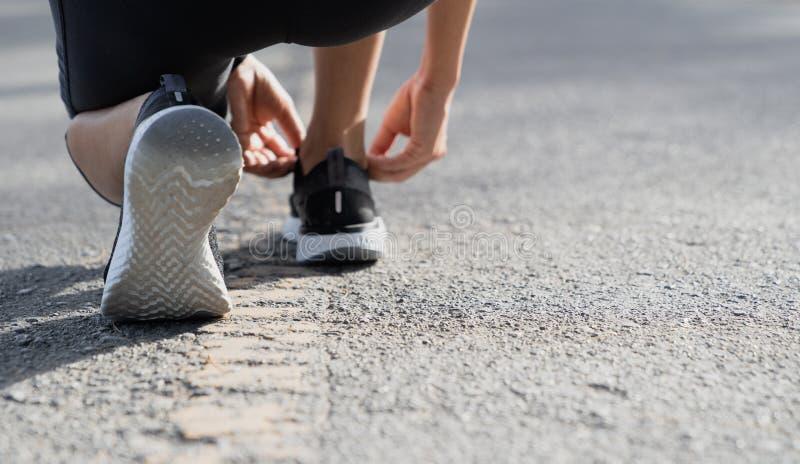 Eine junge Frau gestoppt, um eine Schnur beim Laufen zu binden in das Stadion, Eignungsfrauenläufer, der Spitze vor Betrieb binde stockfoto