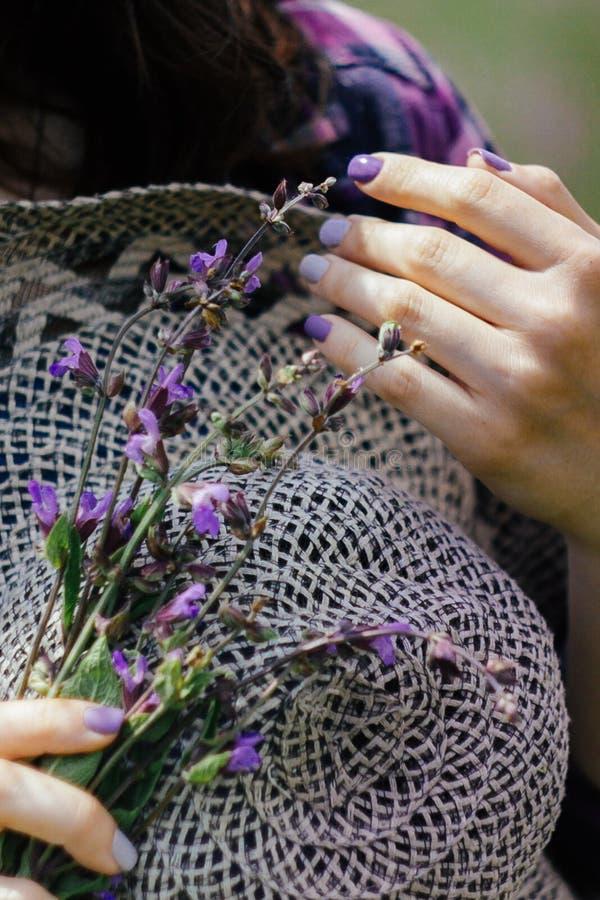 Eine junge Frau h?lt einen Strohhut und einen Blumenstrau? des lila bl?henden Lavendels Violette Stimmung lizenzfreies stockfoto