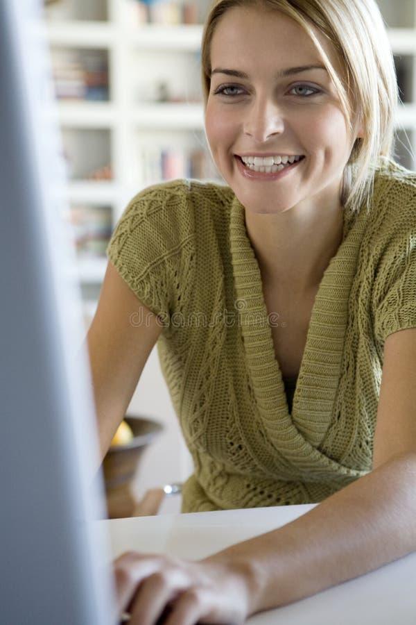 Eine junge Frau an ihrem Computer lizenzfreie stockfotos