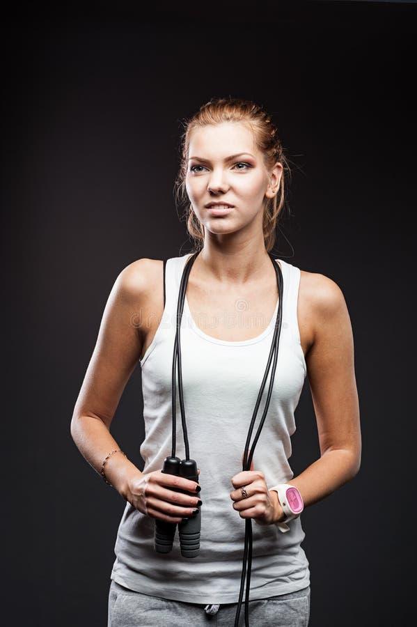 Eine junge Frau im Sportkleidungsbetrieb lokalisiert über grauem Hintergrund stockbilder