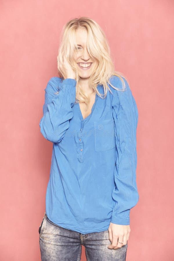 Eine junge Frau, 20-29 Jahre alt, lang blondes Haar Schuss im Studio auf rosa Hintergrund lizenzfreies stockbild