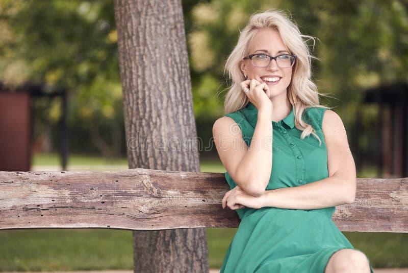 Eine junge Frau, 25 Jahre alt, sitzend in der hölzernen Bank im Park, grünes Kleid, glückliches positives Porträt stockbilder