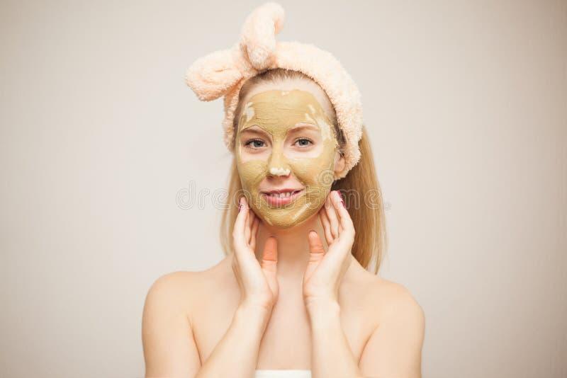 Eine junge Frau macht eine Gesichtsmaske vom Lehm Kosmetische Prozeduren Haupthautpflege stockfotos