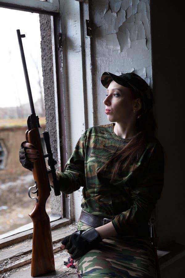 Eine junge Frau mit einem Gewehr in der Uniform am Fenster, welches die Straße betrachtet Der Frauenscharfschütze in einer grünen stockfotografie
