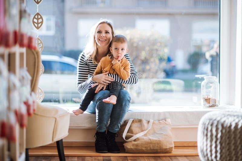 Eine junge Frau mit einem Kleinkindjungen, der im null überschüssigen Geschäft stillsteht lizenzfreies stockbild