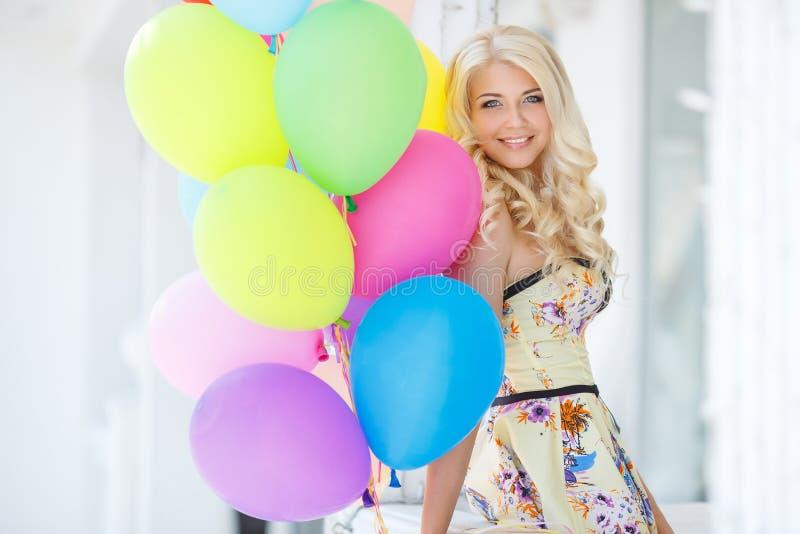 Eine junge Frau mit großem buntem Latex steigt im Ballon auf lizenzfreie stockbilder