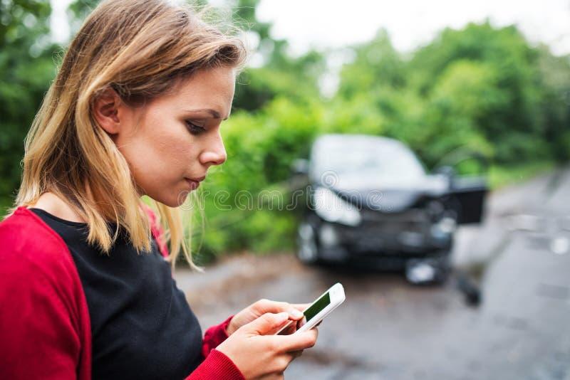 Eine junge Frau mit Smartphone durch das beschädigte Fahrzeug nach einem Autounfall, Versenden von SMS-Nachrichten lizenzfreies stockfoto