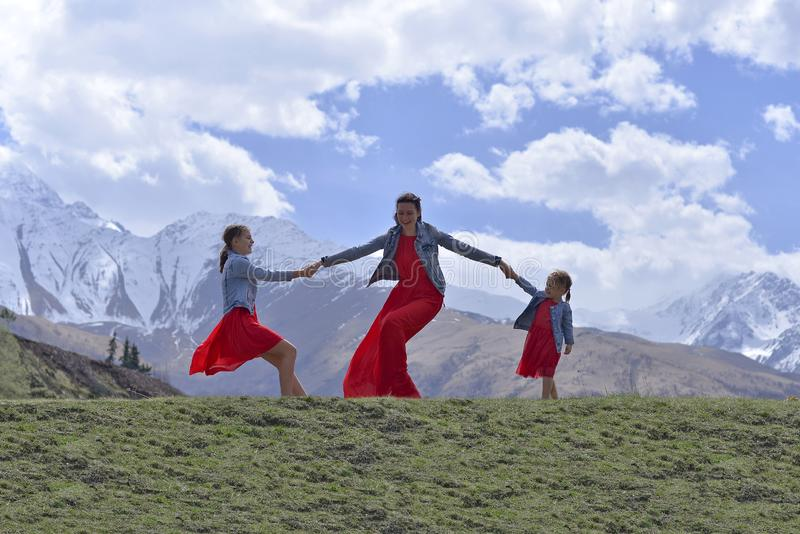 Eine junge Frau mit zwei Töchtern in den roten Kleidern, die im Frühjahr in den Schnee-mit einer Kappe bedeckten Bergen stillsteh lizenzfreies stockfoto