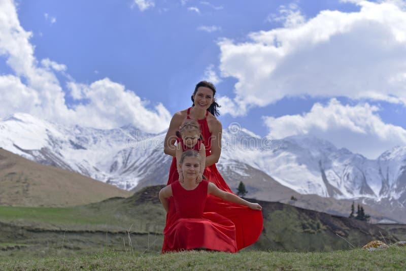 Eine junge Frau mit zwei T?chtern in den roten Kleidern, die im Fr?hjahr in den Schnee-mit einer Kappe bedeckten Bergen stillsteh lizenzfreies stockfoto