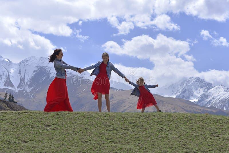 Eine junge Frau mit zwei T?chtern in den roten Kleidern, die im Fr?hjahr in den Schnee-mit einer Kappe bedeckten Bergen stillsteh lizenzfreie stockfotos
